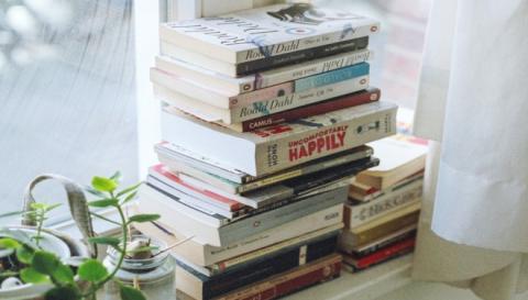 Stack of books on windowsill.