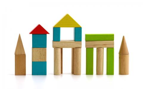 Photograph of wooden building blocks shaped as buildings.
