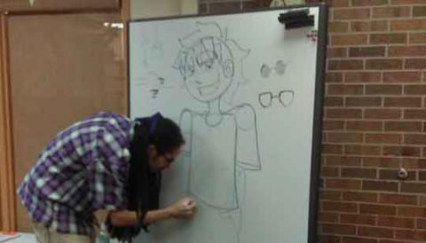 Artist demonstrating how to draw on a white board