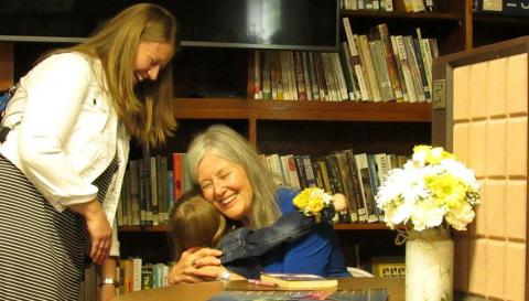Author Elizabeth Berg hugs a girl at her Meservey Public Library visit