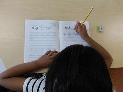 An overhead view of a child practicing cursive writing at a desk