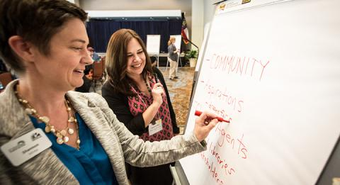 Women write on a white board at a Public Innovators Lab for Libraries