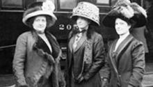 Suffragettes Mrs. Fred Lorenz, Mrs. Ella S. Stewart, and Miss Bertha Seass standing on a railroad platform.  Chicago History Museum