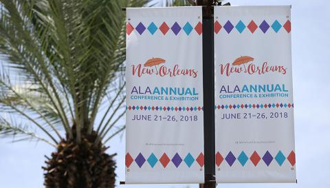 "A street banner that reads ""New Orleans - ALA Annual Conference, June 21-26-2018"""
