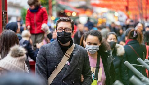 people walking in a crowd wearing face masks