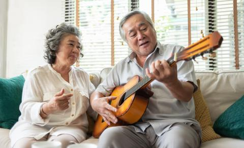 Photograph of senior couple playing guitar on a couch