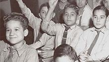 Children in desks raising hands (Library of Congress)