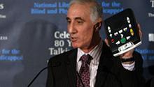 Materials Development Division chief Michael Katzmann displays an NLS digital talking book machine.