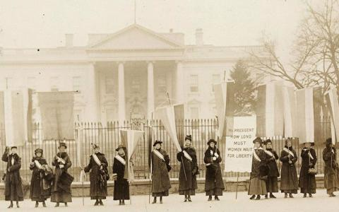 Black and white photo of suffragettes in front of the white house.