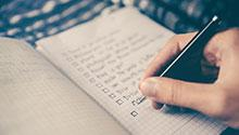 Hand checking off a to-do list in a notebook