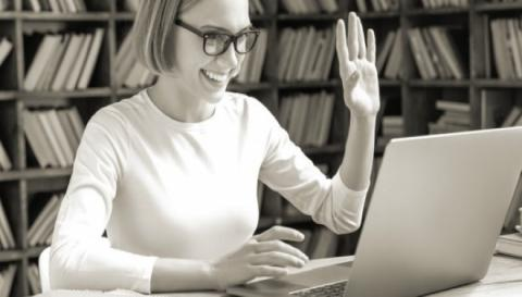 Woman smiling and waving to laptop screen