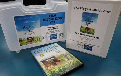 """Photograph of a Film Discussion Kit for """"The Biggest Little Farm."""" Photograph shows the DVD, Film Discussion Guide binder, and container."""