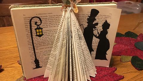 Book standing up open with the pages folded to form a triangle fan with black paper cut and pasted to the open pages to look like two people walking by a street lamp.