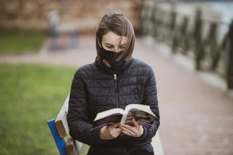 A woman wearing a mask reading on a park bench