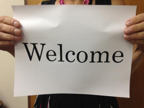 "Hands holding up a ""welcome"" sign"