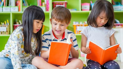 Three children sitting down and looking at books