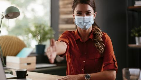 Photograph of woman in medical mask reaching hand out for handshake.