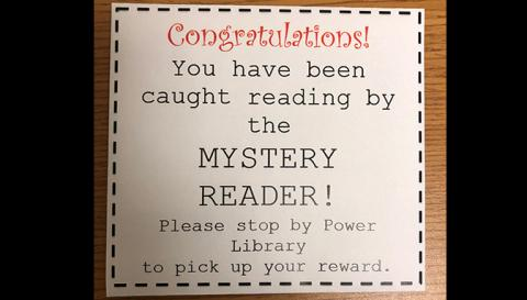 "Slip that reads ""Congratulations! You have been caught reading by the mystery reader! Please stop by Power Library to pick up your reward."""