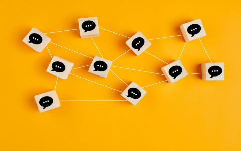 Photograph of connected chat bubbles on a yellow background.