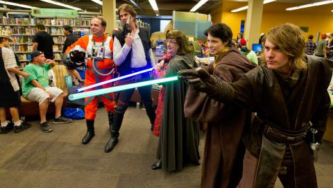 Cosplayers in costume, holding light sabers