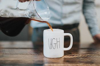 "Pouring coffee into a mug that says ""ugh"""