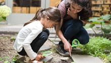 An instructor teaches a little girl about nature.