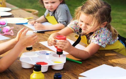 Photograph of kids painting outside.