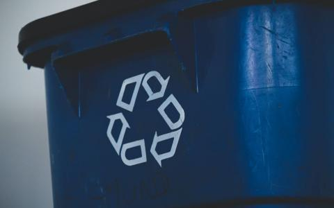 Photograph of blue recycling bin with the recycling logo.