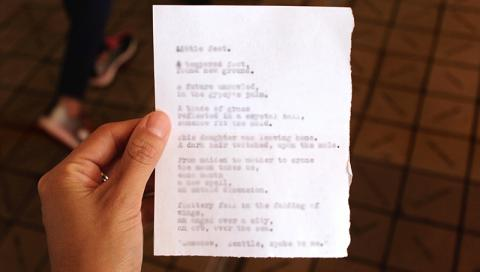 Hand holding paper with poem written on it
