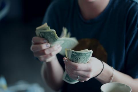 A person counting dollar bills