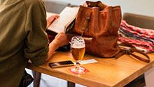 Woman reading book next to glass of beer