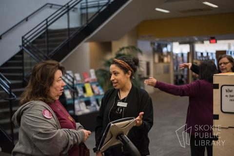 A librarian discusses the Civic Lab topic with a patron.