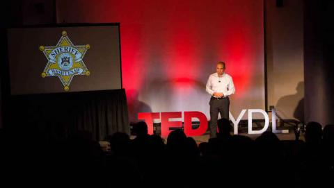 Speaker at TedxYDL next to PowerPoint presentation