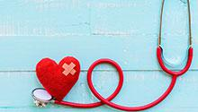 Red stethoscope with red felt heart on turquoise background