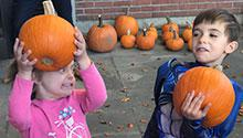Two children holding pumpkins