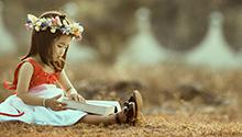 Little girl reading a book outside photo by MI PHAM on Unsplash