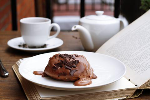 A small chocolate cake sits on a plate on top of an open book. A tea cup and tea pot are in the background.