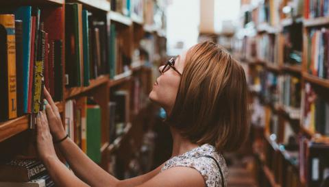 A woman looks for a book in the stacks.