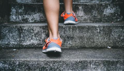 Photo of someone walking up stairs; zoomed in on sneakers.