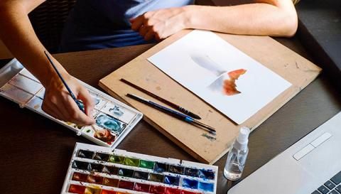 Photo of a person painting in watercolor.