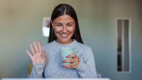 A woman holding a coffee cup smiling at a computer screen
