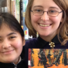 """A librarian and a student hold a copy of """"March: Book One"""""""