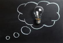 A thought bubble is drawn around a light bulb on a chalkboard.