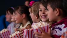 kids watching a movie with popcorn