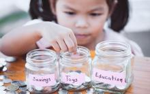 Photograph of child putting coins into three jars. Jars are labeled: Savings, Toys, Education