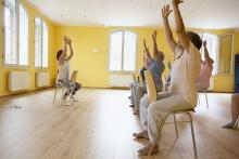 Women sitting in chairs in a row with their arms raised, exercising.