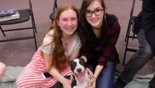 Two smiling girls pose with a happy puppy