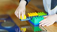 Hands of child playing with construction blocks