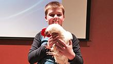 Presenter's son holding chicken at talk about chicken-raising
