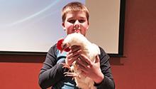 Presenter's son holding chicken at talk about chicken-raising